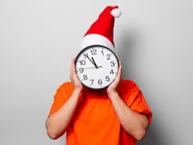 Man with Christmas hat and big clock. Young handsome man in orange t-shirt with Christmas hat and big clock. Studio image on white background Stock Image
