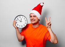 Man with Christmas hat and big clock. Young handsome man in orange t-shirt with Christmas hat and big clock. Studio image on white background Royalty Free Stock Image
