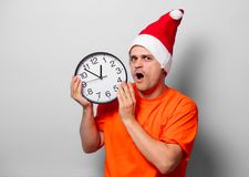 Man with Christmas hat and big clock. Young handsome man in orange t-shirt with Christmas hat and big clock. Studio image on white background Royalty Free Stock Photos