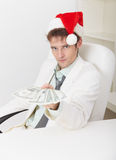 Man in Christmas hat gives us money Stock Photos