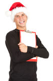 Man in Christmas hat keeping blank clipboard Royalty Free Stock Image