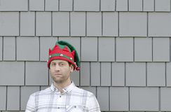 Man in a Christmas hat looking to the side with a smirk. Man in a Christmas hat looking to the side with a smirk standing in front of a gray background Stock Photography