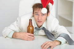 Man in Christmas hat at office with a beer bottle Royalty Free Stock Images