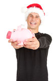 Man in Christmas hat putting five euro in piggy ba Royalty Free Stock Images
