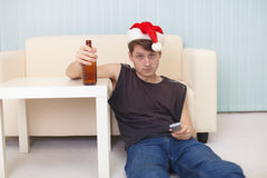 Man in christmas hat sits on a floor with beer Stock Image