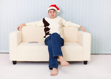 Man in Christmas hat sits on sofa and watches TV Royalty Free Stock Photo
