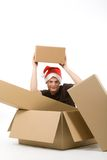 Man with christmas packages. Young man with a christmas cap sits in a carton and lift up another one blank package (blank for your own text Stock Photo