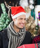 Man With Christmas Present Smiling In Store Royalty Free Stock Images