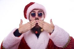 a man with Christmas toys in a beard and in a suit of Santa Claus holds his hands near his lips stock photos