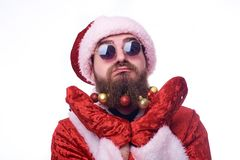 A man with Christmas toys in a beard and in a suit of Santa Claus holds his hands under his head and squirms his face royalty free stock photo