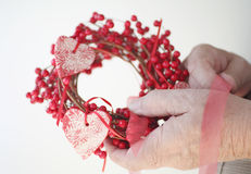 Man with Christmas wreath of berries, hearts Stock Images