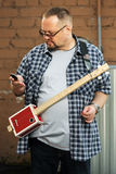 Man with a cigar box guitar looking at cell phone Royalty Free Stock Images