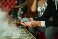 Man with cigar counting money in the club. Group of young multi-ethnic friends relaxing in shisha club-bar in rich. Interior stock image