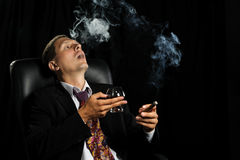 The man with a cigar and a glass of cognac Royalty Free Stock Images