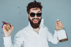 Man with cigar partying in studio. Handsome male with beard and sunglasses having fun royalty free stock image