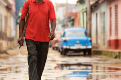 Man with cigar walking on street of Trinidad, Cuba Stock Photography