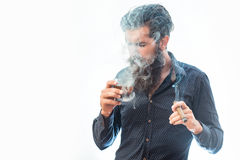 Man with cigar and whiskey. Handsome bearded tough rich man with stylish hair mustache and long beard on serious face in blue fashion shirt smoking cigar and royalty free stock image