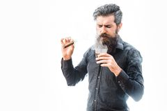 Man with cigar and whiskey. Handsome bearded tough rich man with stylish hair mustache and long beard on serious face in blue fashion shirt smoking cigar and stock photos