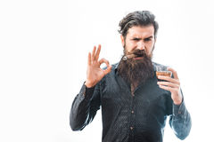 Man with cigar and whiskey. Handsome bearded tough rich man with stylish hair mustache and long beard on serious face in blue fashion shirt smoking cigar holding royalty free stock image
