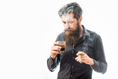 Man with cigar and whiskey. Handsome bearded tough rich man with stylish hair mustache and long beard on serious face in blue fashion shirt smoking cigar and royalty free stock photo