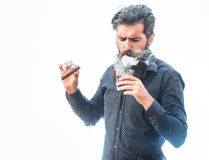 Man with cigar and whiskey. Handsome bearded tough rich man with stylish hair mustache and long beard on serious face in blue fashion shirt smoking cigar and royalty free stock images