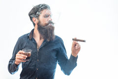 Man with cigar and whiskey. Handsome bearded tough rich man with stylish hair mustache and long beard on serious face in blue fashion shirt smoking cigar and stock photo