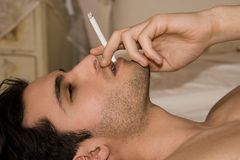 Man with cigarette. Man lying on the bed lighting a cigarette Royalty Free Stock Photo