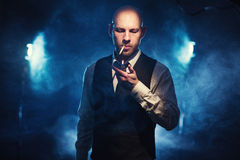 Man with a cigarette and lighter against a dark background. Bald man with a cigarette and lighter against a dark background Stock Images