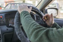 A man driving a car holding a cigarette. A man with a cigarette sitting behind the wheel of a car. Bad habit stock photo