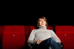 Man in the cinema. Young man in casual sitting in the cinema and watching a movie Royalty Free Stock Photo