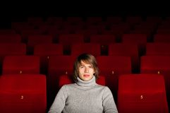 Man in the cinema. Young man in casual sitting in the cinema and watching a movie Stock Photos