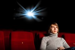 Man in the cinema. Young man in casual sitting in the cinema and watching a movie Royalty Free Stock Photography
