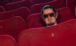 Man in cinema. Funny young man in 3D glasses watching movie in cinema stock photography