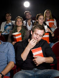 Man at the cinema with popcorn Stock Images