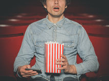Man in cinema watching movie and using his phone Royalty Free Stock Photo