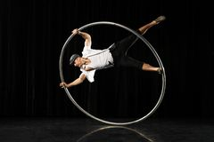 Man with circle at black background. Circus performer artist in a Cyr Wheel Roy Cyr in theatre at a black background Stock Image