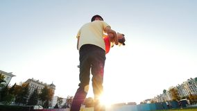 Man circling his little daughter in his arms in the park on a warm summer evening stock footage