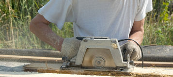 The man with a circular saw. The man saws a board a circular power saw Royalty Free Stock Image