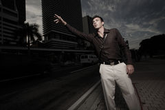 Man in the city hailing a cab Royalty Free Stock Image