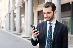 Man in the city looking at his smart phone Royalty Free Stock Image