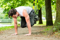 Man in city park doing suspension trainer sport Royalty Free Stock Photo