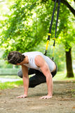 Man in city park doing suspension trainer sport Royalty Free Stock Photography