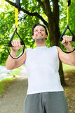 Man in city park doing suspension trainer sport Stock Photos