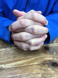 Man with clasped hands. Man with clasped or interlocked hands sitting at a table Stock Photos
