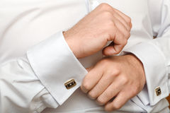 The man clasps a cuff link. On a shirt Stock Image