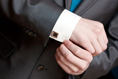 The man clasps cuff link on a shirt Stock Photos