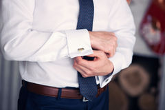 The man clasps cuff links on a shirt Royalty Free Stock Photo