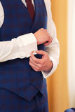 The man clasps cuff links on a shirt. The man in a red tie clasps cuff links on shirt cuffs royalty free stock photos