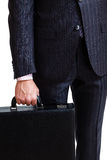 A man in a classic suit holds a black briefcase Royalty Free Stock Photography