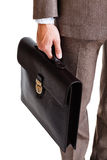 A man in a classic suit holds a brown briefcase Stock Images